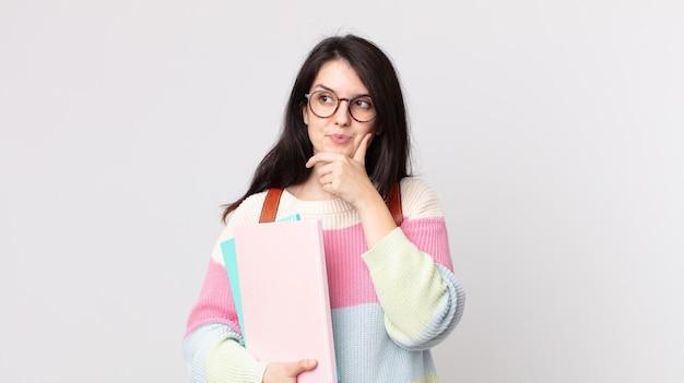 Красивая женщина улыбается с счастливым, уверенным выражением лица, положив руку на подбородок. концепция студента университета