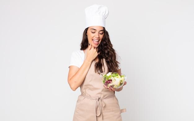 Красивая женщина улыбается со счастливым, уверенным выражением лица, положив руку на подбородок, в фартуке и держит салат