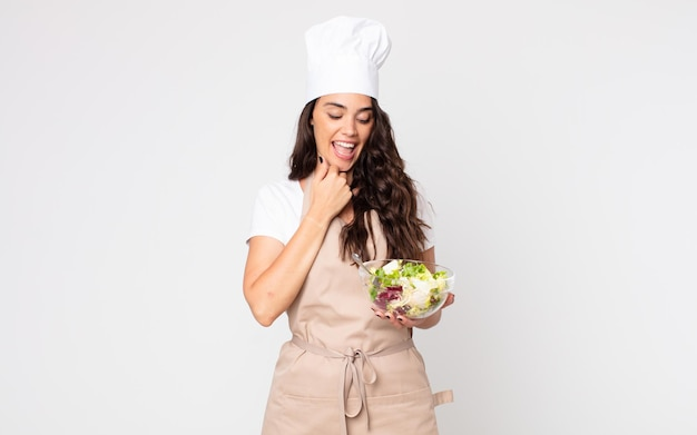 Pretty woman smiling with a happy, confident expression with hand on chin wearing an apron and holding a salad