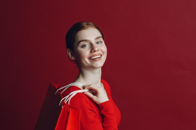 빨간 종이 쇼핑백과 예쁜 여자 smilng 초상화.