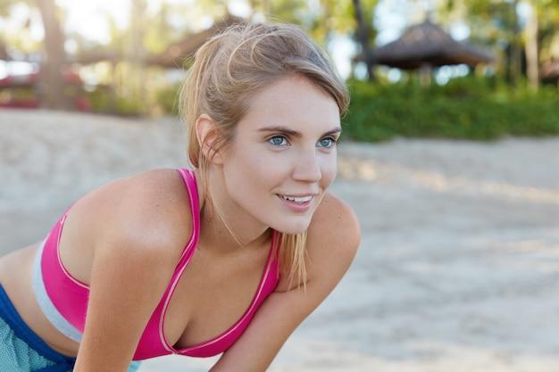 Bella donna in abiti sportivi sulla spiaggia