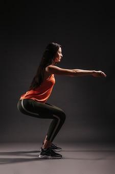 Pretty woman squatting on dark background