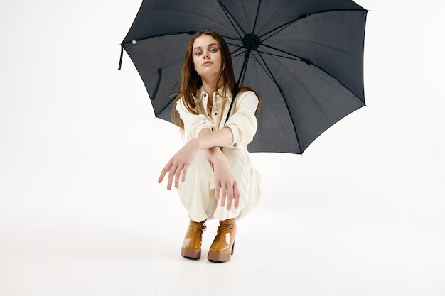 Pretty woman squatting open umbrella fashion modern style.