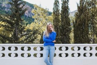 Pretty woman standing on terrace near forest