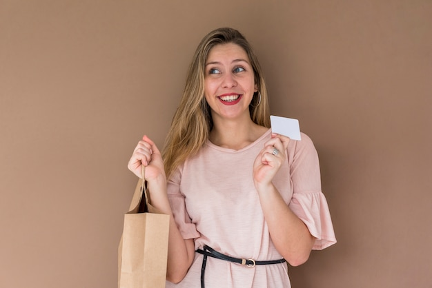 Pretty woman standing with shopping bag and credit card