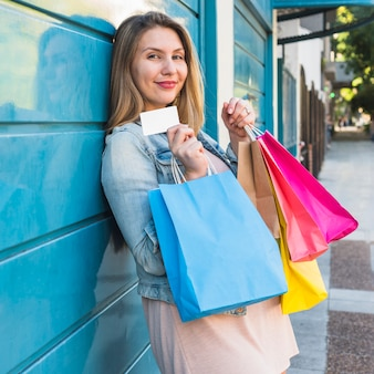 Pretty woman standing with shopping bags and credit card