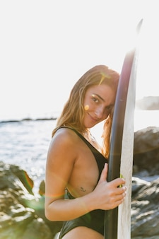 Pretty woman standing with surfboard on sea shore