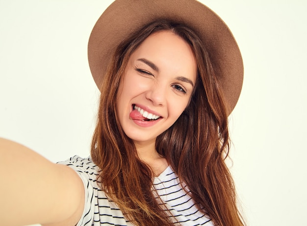 Pretty woman in summer hipster clothes take selfie from hands with phone, showing her tongue