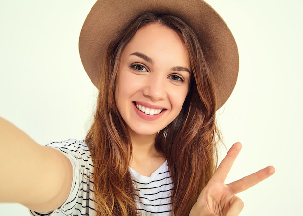 Pretty woman in summer hipster clothes take selfie from hands with phone