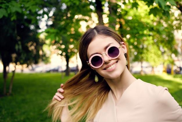 公園の緑の草モデルのきれいな女性のサングラスと帽子