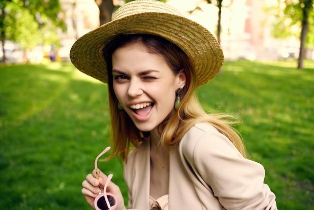 公園の緑の芝生できれいな女性のサングラスと帽子