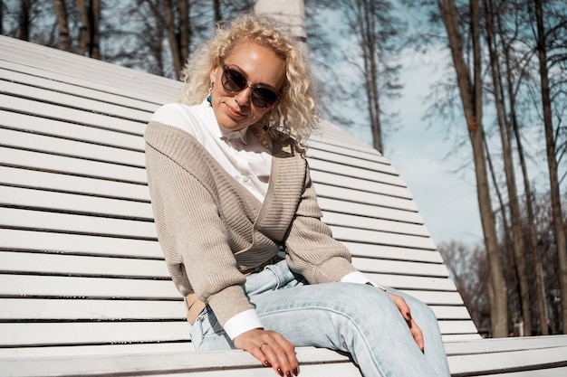 Pretty woman in sunglasses on bench at autumn park alone, lifestyle people concept