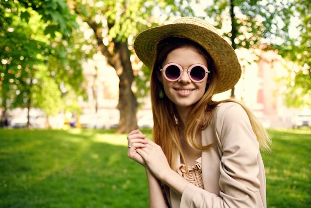 Pretty woman in sunglasses and a hat outdoors in the park rest. high quality photo