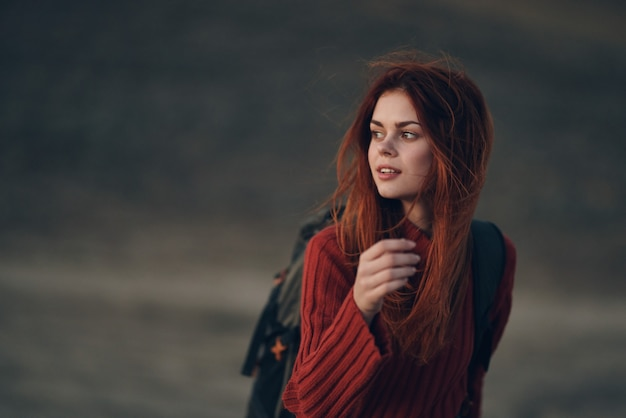 Pretty woman in a sweater with a backpack are walking in nature in the mountains on a meadow. high quality photo