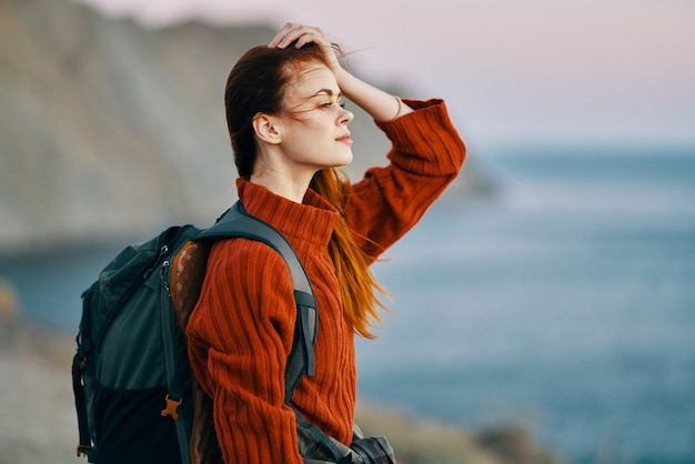 Pretty woman in a sweater with a backpack on her back and sea mountains nature fresh air. high quality photo