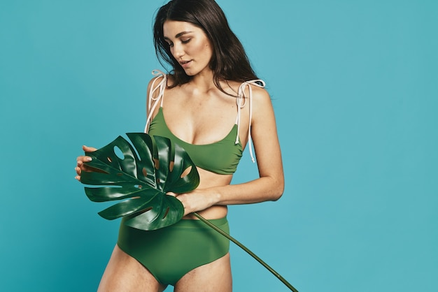 Pretty woman in swimsuit palm leaf exotic summer beach. high quality photo