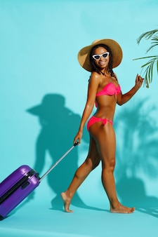 Pretty woman in swimsuit poses with suitbag on blue