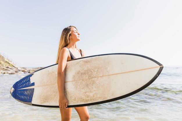 Pretty woman in swimsuit walking with surfboard in sea