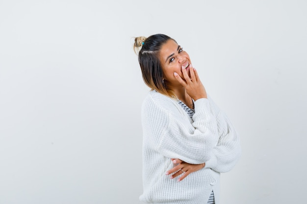 Pretty woman in t-shirt, cardigan posing with hand near mouth and looking jovial