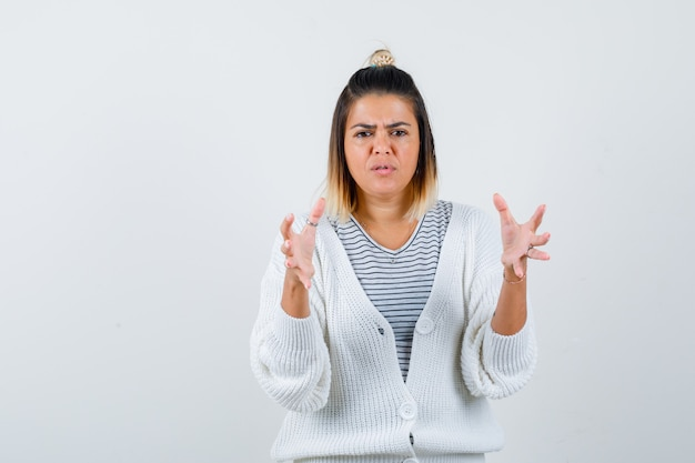 Pretty woman in t-shirt, cardigan showing size sign and looking confused