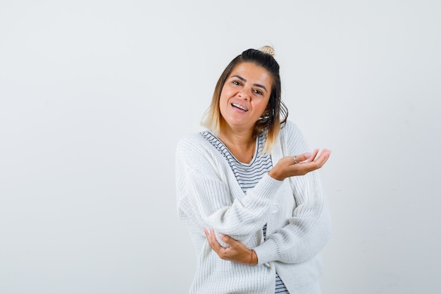 Bella donna in t-shirt, cardigan che allarga il palmo e sembra confusa