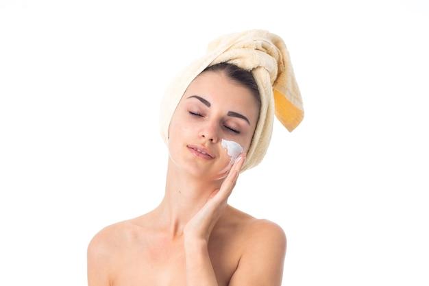 예쁜 여자는 흰 벽에 고립 된 크림으로 얼룩진 머리에 수건으로 그녀의 피부를 돌 봅니다.