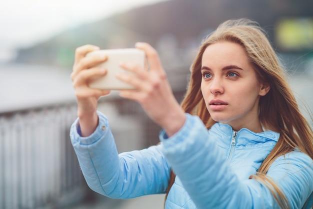 예쁜 여자는 selfie를 복용입니다. 거리를 걷고 몇 가지 랜드 마크를 촬영하는 아름다운 소녀. 자신의 금발 촬영 사진