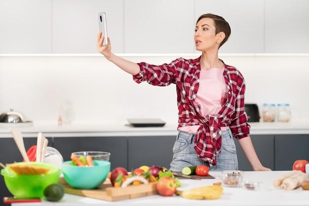 Красивая женщина делает селфи или делает видеозвонок, используя свой смартфон, держа его в вытянутой руке