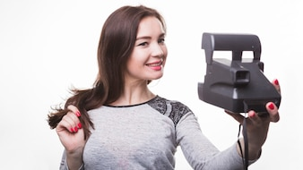 Pretty woman taking selfie with instant camera