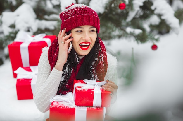 Pretty woman talking on a mobile phone and holding christmas presents.