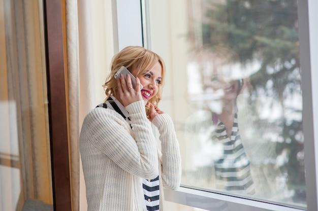 Красивая женщина разговаривает по телефону возле окна, блондинка