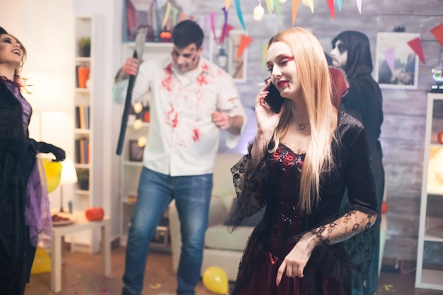 Pretty woman talking on the phone at halloween party dressed up like a vampire.
