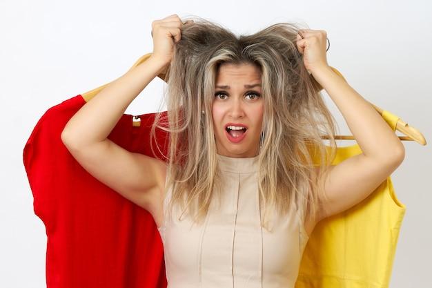 Красивая женщина рвет волосы, потому что не может выбрать платье