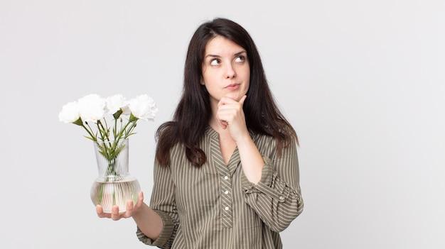 考えて、疑わしくて混乱していて、装飾的な花を持っているきれいな女性。ヘッドセット付きのアシスタントエージェント