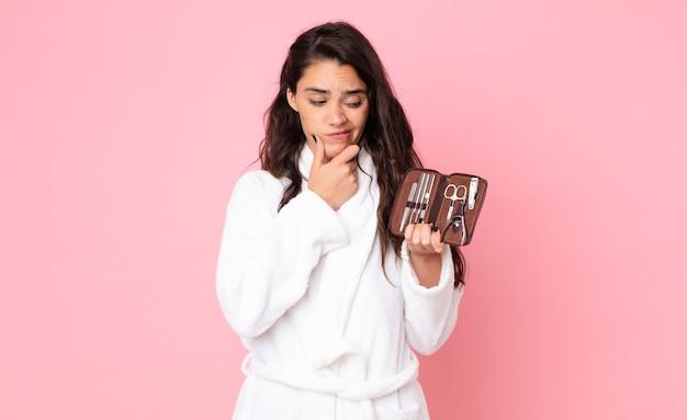 Красивая женщина думает, чувствует себя сомнительно и смущенно и держит сумку для макияжа с инструментами для ногтей