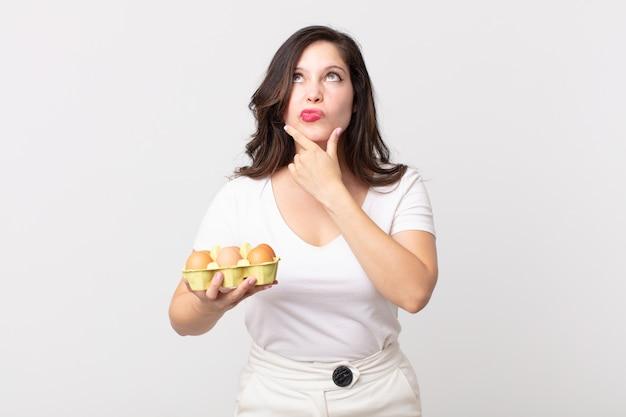 Красивая женщина думает, сомневается и смущается и держит коробку для яиц