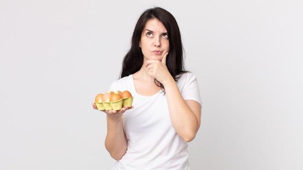 예쁜 여자가 생각하고, 의심스럽고 혼란스러워하며 계란 상자를 들고 있다