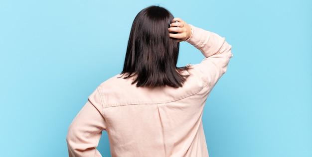 Симпатичная женщина думает или сомневается, почесывает голову, чувствует недоумение и замешательство, вид сзади или сзади