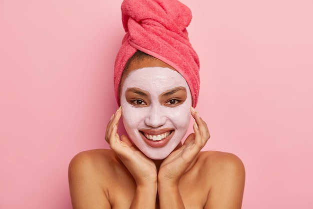 Pretty woman touches face gently, wears facial mask for refreshing skin, has healthy complexion, wears pink towel, has cosmetic treatments, stands indoor. femimity, spa, relaxation