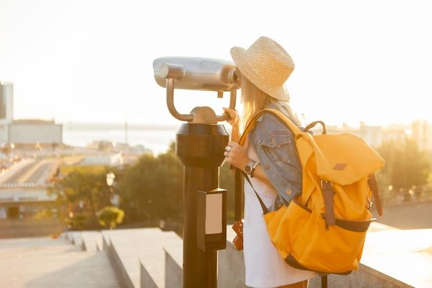 プリティウーマンの観光客は、都市の双眼鏡を通して見ています。旅行と観光のコンセプト。新しい場所を発見する