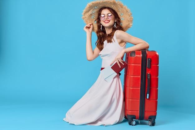 Красивая женщина турист в шляпе красный чемодан отпуск синий фон