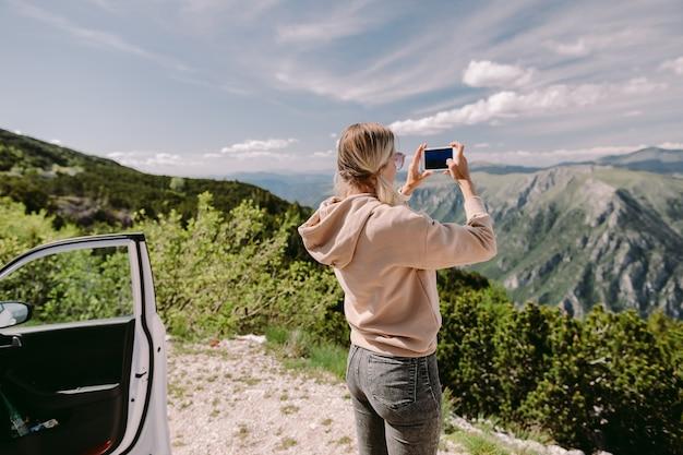 きれいな女性が車で旅行し、山でのロードトリップ休暇でスマートフォンを使用しています。