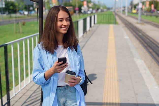 Pretty woman uses smart phone and drinks morning coffee to go while waiting tram or bus on the public station.