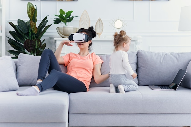 Pretty woman uses virtual reality goggles at home on sofa while her daughter watches cartoons on laptop