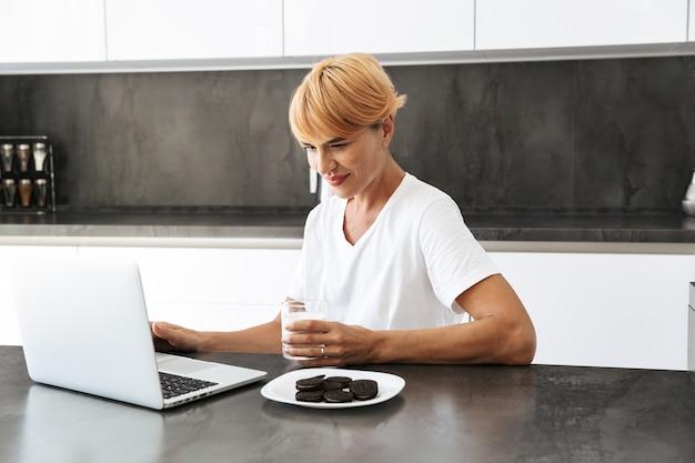 Красивая женщина с портативным компьютером, сидя за кухонным столом, пьет молоко из стакана, ест печенье