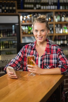 Pretty woman using smartphone and having a beer