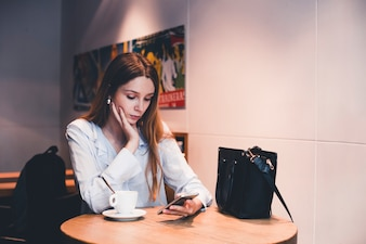 Pretty woman using smartphone in cafe