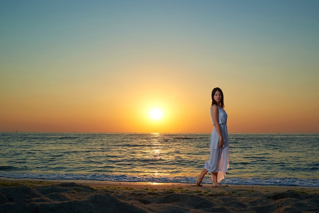 Pretty woman walking along the sea shore. girl wearing long white dispersing on wind dress.