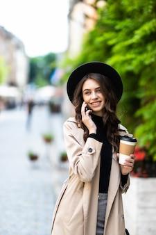 예쁜 여자 걷고 화창한 여름 날에 거리에서 스마트 폰으로 이야기