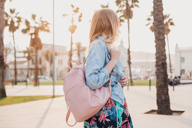 Bella donna che cammina nella strada della città in elegante giacca oversize in denim, che tiene zaino in pelle rosa, tendenza stile estivo